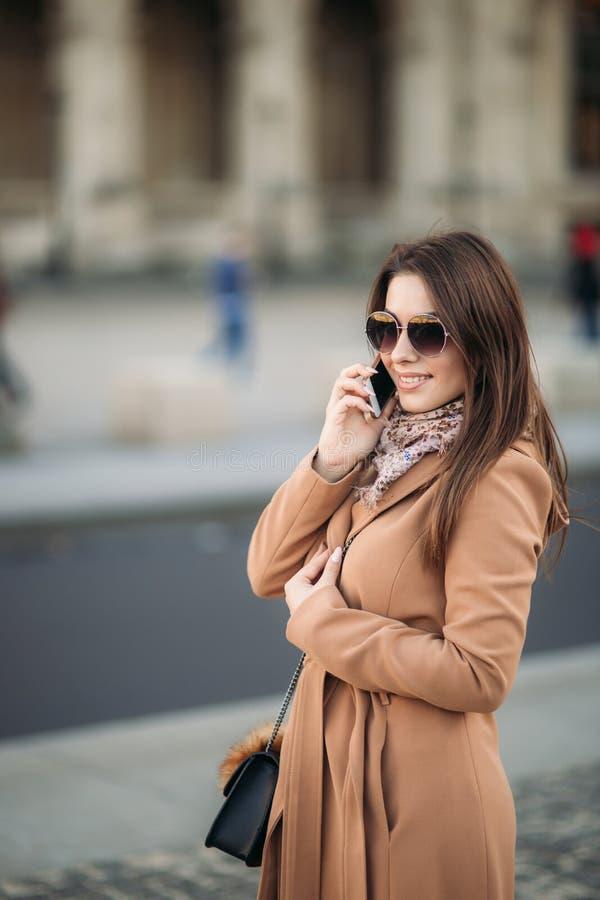 Atrakcyjny dziewczyny use telefon w centre miasto jesień spadek przyjaciele leaf pod spaceru pogody drewnem obrazy stock