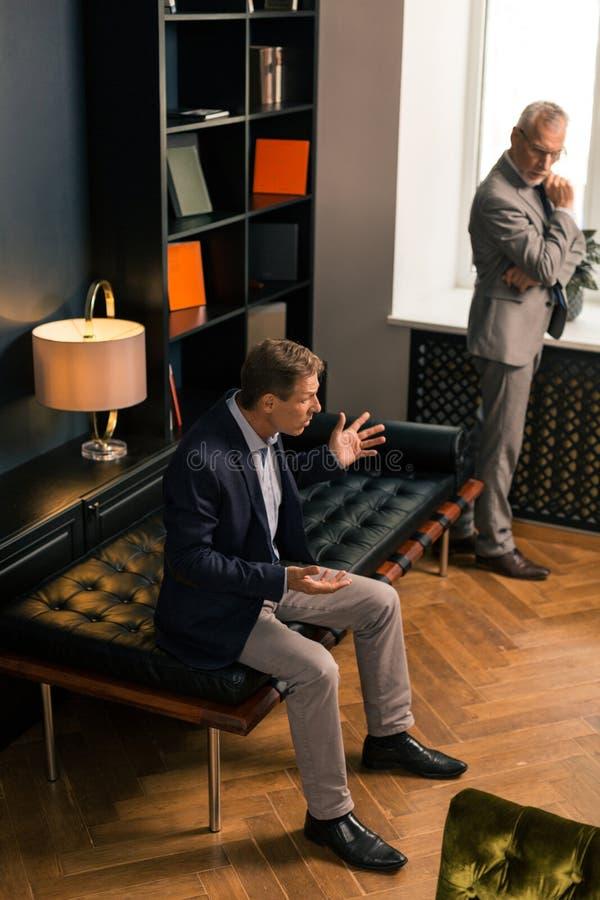Atrakcyjny elegancki baczny psycholog stoi bezczynnie okno zdjęcie stock