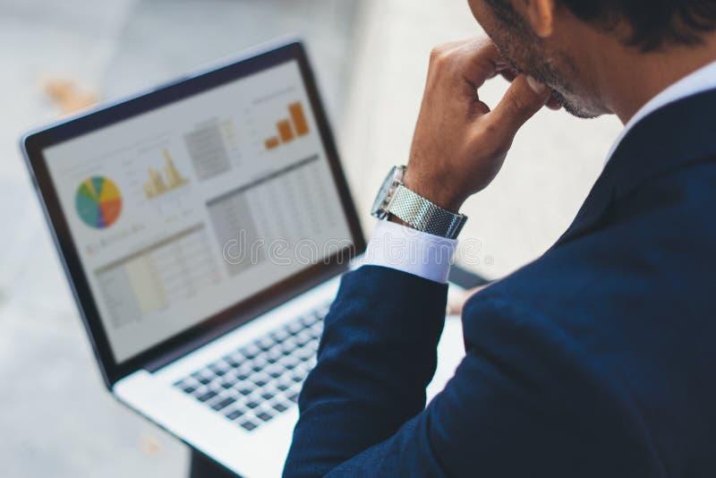 Atrakcyjny elegancki biznesmen używa współczesnego notatnika obsiadanie na zewnątrz biura Wykresy i diagramm na laptopie obraz stock