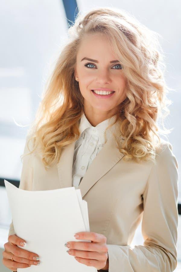 Atrakcyjny elegancki bizneswoman w beżowej kurtce, trzyma papierowy w ręce fotografia stock