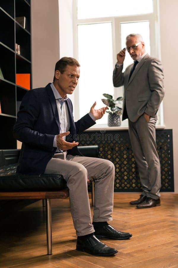 Atrakcyjny elegancki psychoterapeuta ogląda jego pacjenta zmartwionego zachowanie fotografia stock