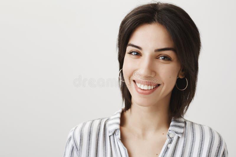 Atrakcyjny europejski sklepowy asystent ono uśmiecha się w eleganckich kolczykach, bluzce i podczas gdy ono wpatruje się przy kam zdjęcia royalty free