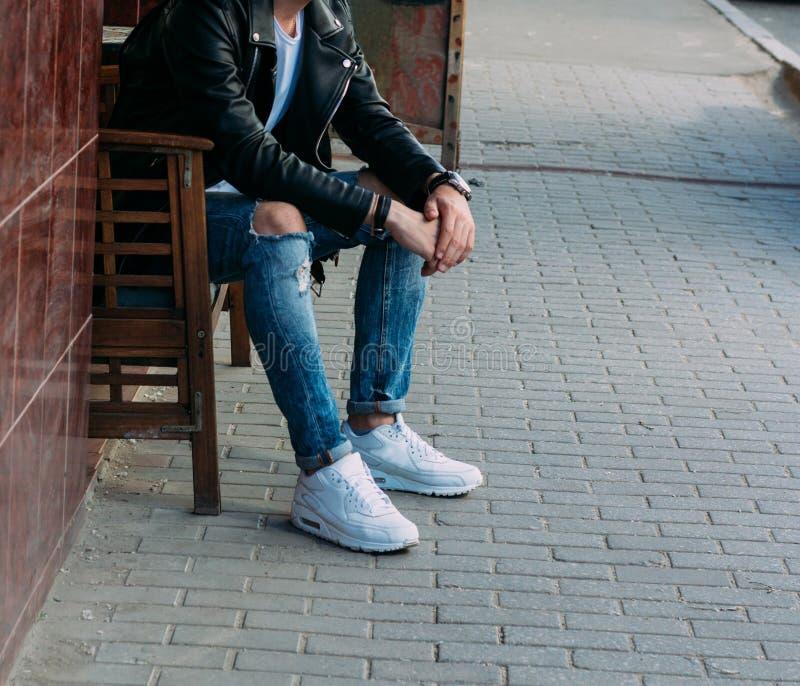 Atrakcyjny faceta obsiadanie na ławce w kawiarni na ulicie, białych sneakers, biała koszulka, czarna skórzana kurtka i czarni caj obraz stock