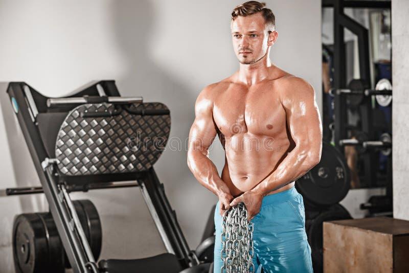 Atrakcyjny hunky czarny męski bodybuilder robi bodybuilding pozie w gym z żelaznymi łańcuchami obraz stock