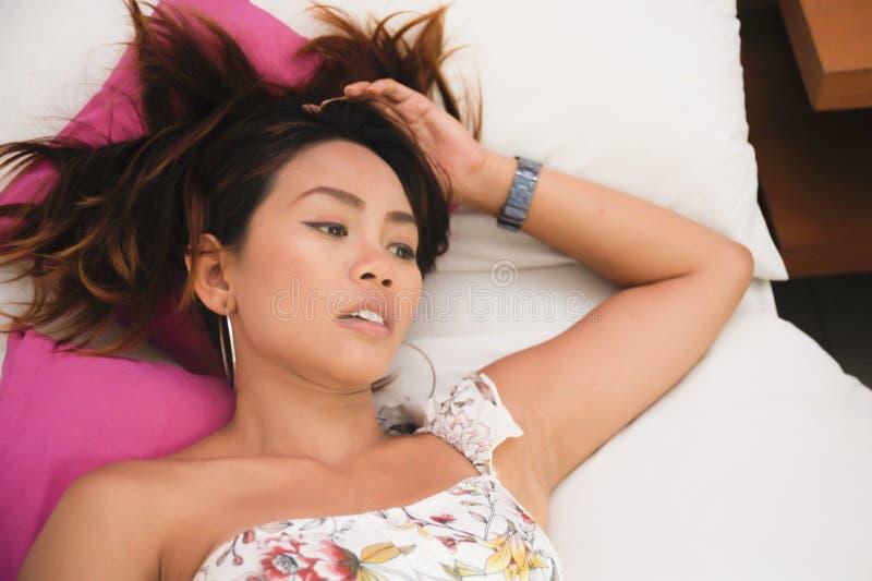 Atrakcyjny i piękny Azjatycki kobiety lying on the beach na łóżku przy sypialnią w piękna indoors studia ustalony patrzeć zdjęcia stock