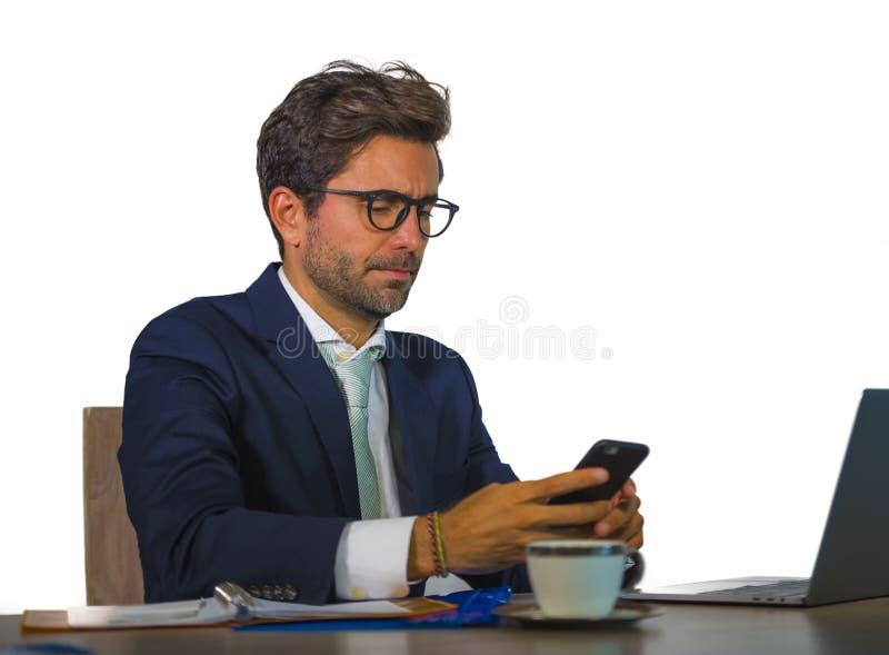 Atrakcyjny i skuteczny biznesowy mężczyzna pracuje przy biurowym laptopu biurkiem ufnym w uśmiechać się szczęśliwego używa telefo obraz royalty free
