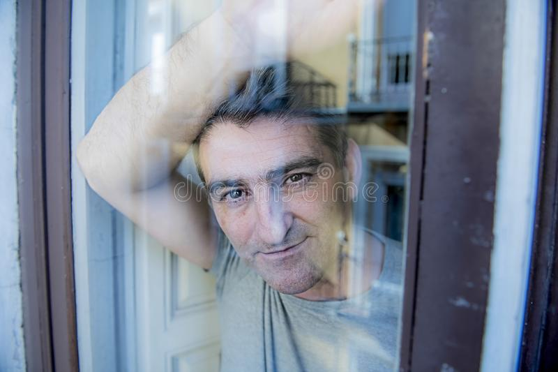 Atrakcyjny i szczęśliwy popielaty włosiany mężczyzna lub spokojny i zadowolony na jego przyglądającego rzutu nadokiennym szkle op fotografia stock