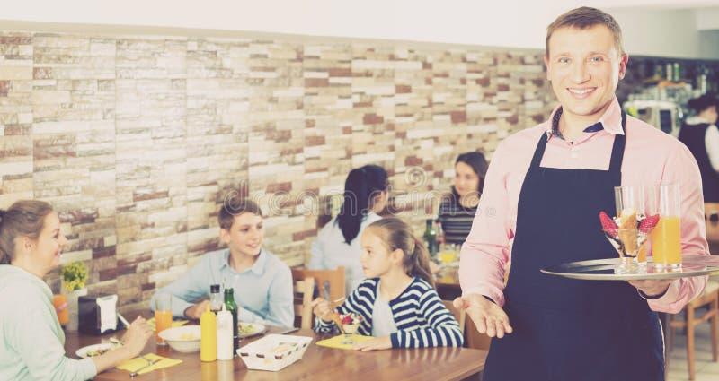 Atrakcyjny kelner pokazuje gościnność i spotyka gości w ca zdjęcia stock