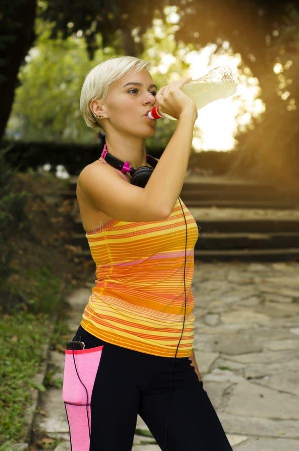 Atrakcyjny kobieta biegacz pije odświeżającego napój zdjęcie royalty free