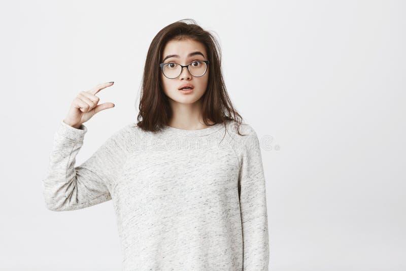 Atrakcyjny kobieta model fotografuje dla promocyjnej kampanii pokazuje coś małego i malutkiego z gestem i obraz royalty free