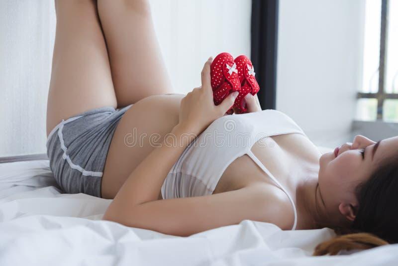Atrakcyjny kobieta w ciąży jest stojący jej brzucha i trzymający Atrakcyjny kobieta w ciąży trzyma dziecka pierwszy buty na jej b obrazy royalty free