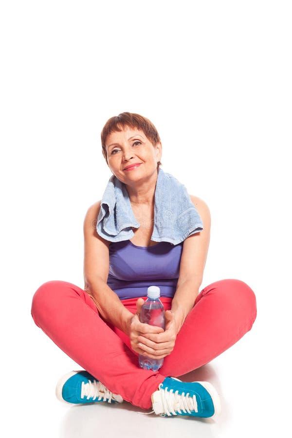 Atrakcyjny kobiety 50 lat z butelką woda obraz stock
