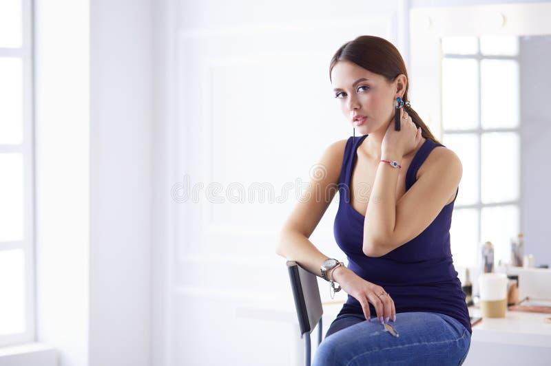Atrakcyjny kobiety obsiadanie na krze?le w salonie fotografia royalty free