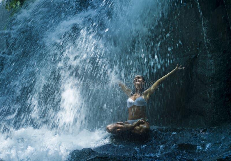 Atrakcyjny kobiety obsiadanie przy skałą w joga pozie dla duchowego relaksu spokoju, medytaci przy oszałamiająco piękną siklawą i obrazy royalty free