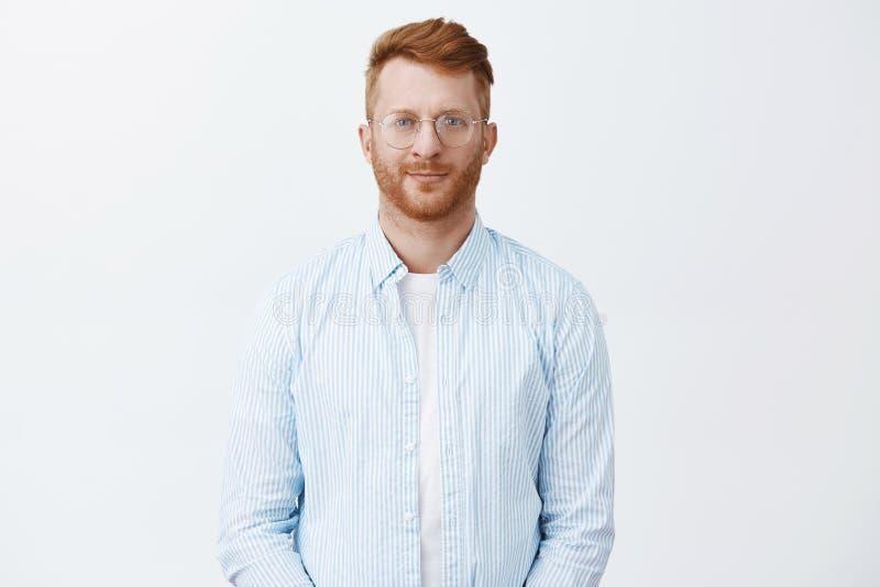 Atrakcyjny kreatywnie i mądrze rudzielec męski przedsiębiorca zatrudnia nowych pracowników, stojący w przypadkowej koszula i szkł fotografia stock