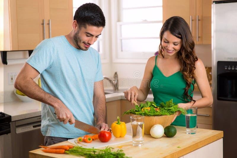 Atrakcyjny mężczyzna i kobieta przygotowywa niskokalorycznego gościa restauracji w kuchennych prawdziwych zdrowie świadomych obraz royalty free