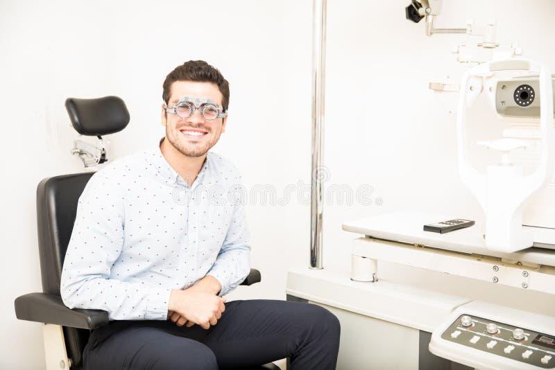 Atrakcyjny mężczyzna obsiadanie na oka testowanie krześle jest ubranym próby ramę zdjęcia royalty free