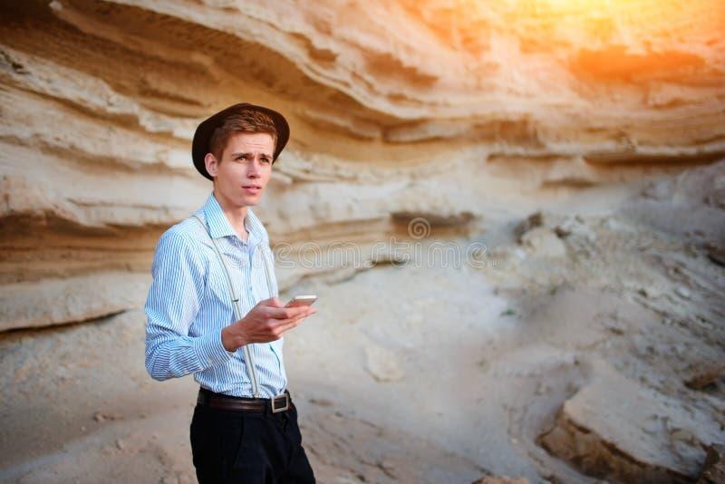 Atrakcyjny mężczyzna patrzeje ekran smartphone na tle piaska łup obrazy royalty free