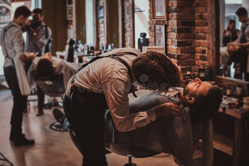 Atrakcyjny m??czyzna w?a?nie dosta? dobrego beardcare od talanted modnego fryzjera m?skiego obraz royalty free