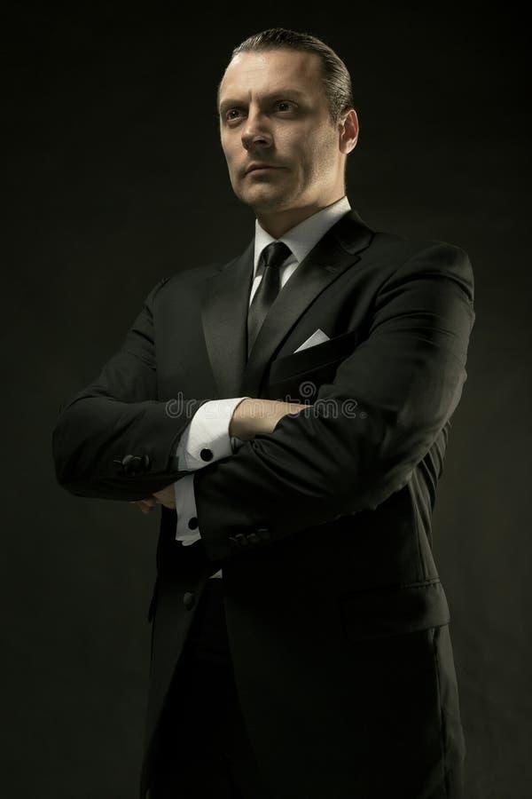 Atrakcyjny mężczyzna w czarnym kostiumu na ciemnym tle fotografia royalty free