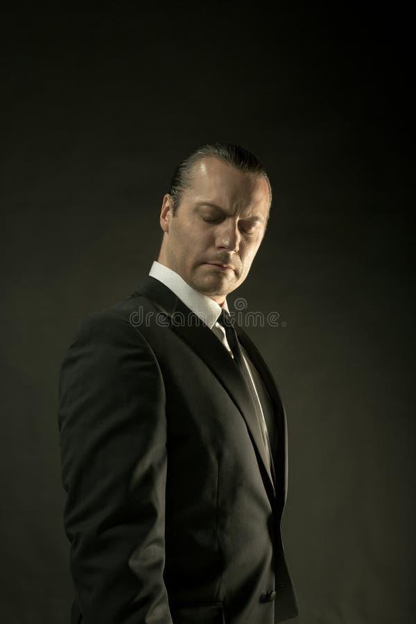 Atrakcyjny mężczyzna w czarnym kostiumu na ciemnym tle zdjęcia stock
