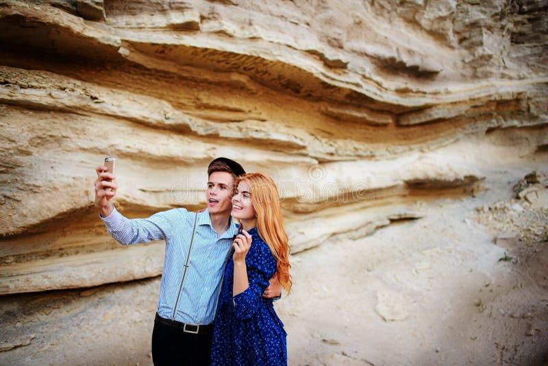 Atrakcyjny mężczyzna z piękną kobietą jest ściskający i uśmiechnięty Robią selfie na tle piaska łup fotografia royalty free
