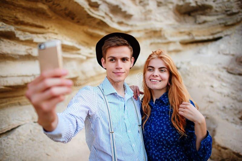 Atrakcyjny mężczyzna z piękną kobietą jest ściskający i uśmiechnięty Robią selfie na tle piaska łup zdjęcie stock