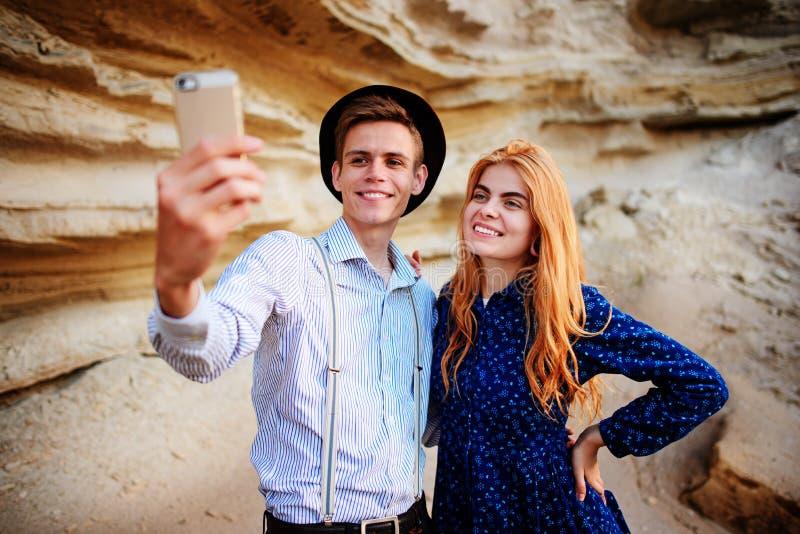 Atrakcyjny mężczyzna z piękną kobietą jest ściskający i uśmiechnięty Robią selfie na tle piaska łup obraz royalty free