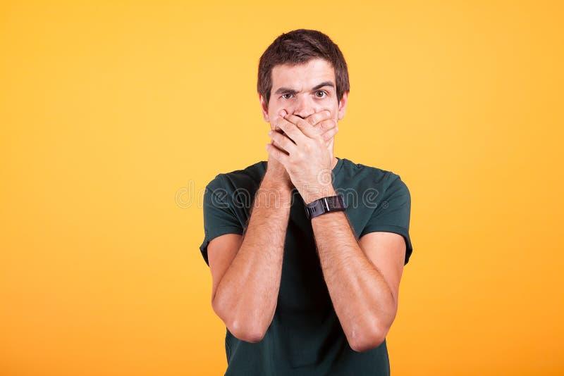 Atrakcyjny mężczyzna zakrywa jego usta w żadny rozmowa znaku na żółtym tle obrazy royalty free