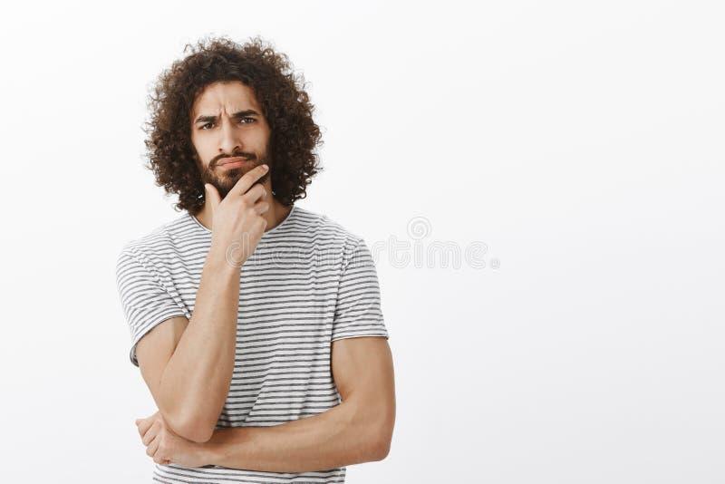 Atrakcyjny męski męski sportowiec z afro ostrzyżeniem marszczy brwi brodę i dotyka, podczas gdy robić decyzi, być zdjęcia stock