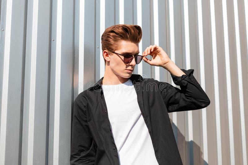 Atrakcyjny młodego człowieka model w modnej czarnej koszula w koszulce prostuje eleganckich okulary przeciwsłonecznych Europejski zdjęcie stock
