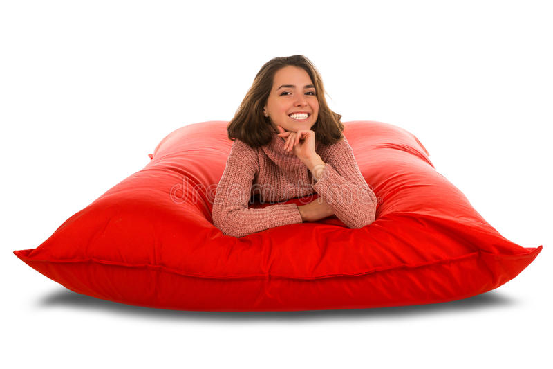Atrakcyjny młodej kobiety lying on the beach na placu czerwonym kształtował beanbag kanapę ja zdjęcia royalty free