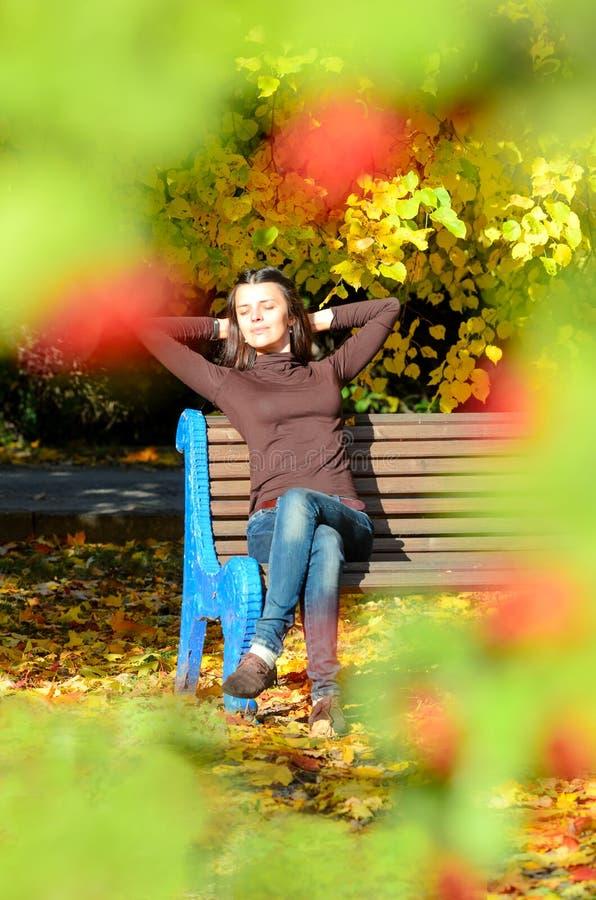Atrakcyjny młodej kobiety obsiadanie na brown drewnianej ławce z rękami za jej głową w pięknym parku Zamykał oczy obraz royalty free