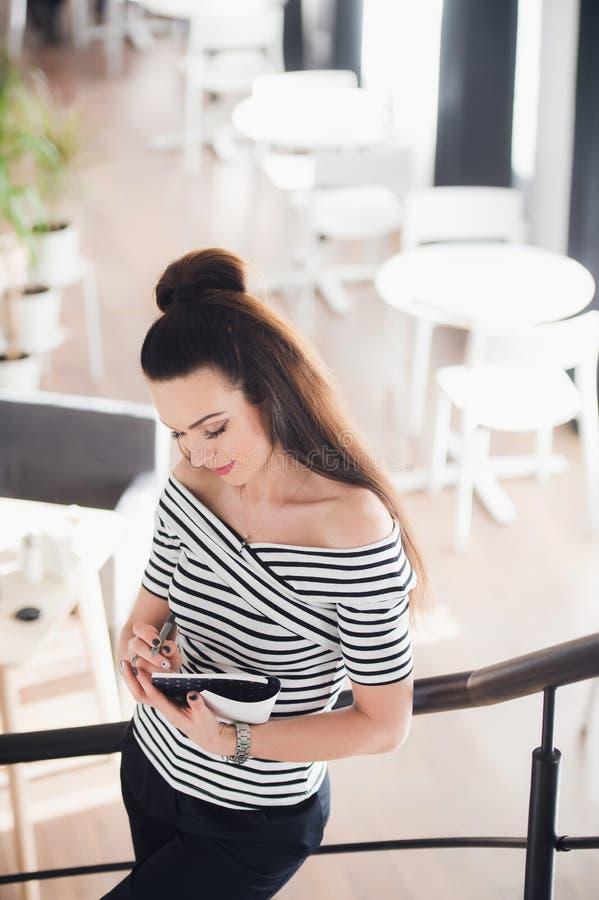 Atrakcyjny młodej kobiety writing w jej notatniku podczas gdy stojący na schodkach w kawiarni i patrzejący w dół zdjęcia stock
