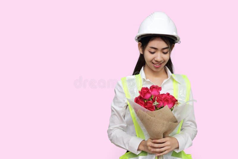 Atrakcyjny młody Azjatycki kobieta inżynier trzyma bukiet czerwone róże na menchiach odizolowywał tło fotografia stock