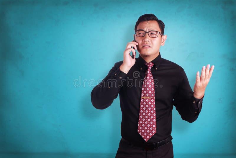 Atrakcyjny młody biznesmen opowiada na jego telefonie zdjęcia royalty free