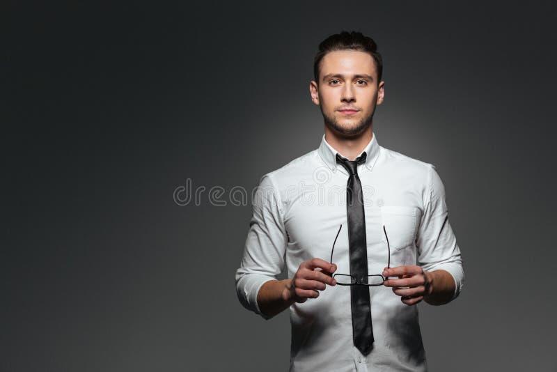 Atrakcyjny młody biznesmen trzyma szkła w białym krawacie i koszula obraz stock