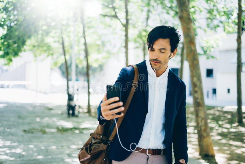 Atrakcyjny młody biznesmen używa smartphone dla listining muzyki w miasto parku podczas gdy chodzący Horyzontalny, zamazany zdjęcie royalty free