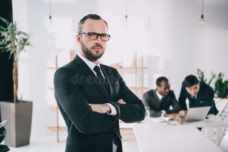 atrakcyjny młody biznesmen z zamazanymi kolegami obraz stock