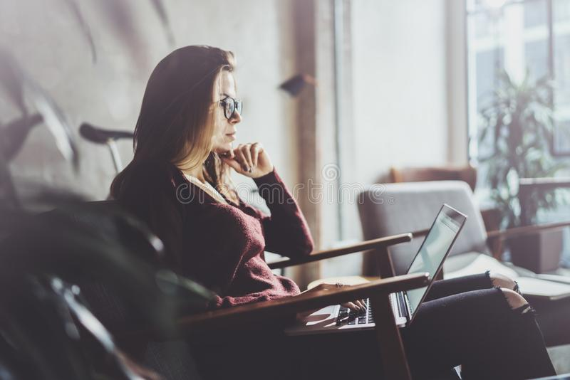 Atrakcyjny młody bizneswoman jest ubranym przypadkowych ubrania i działanie przy coworking biurem Żeńska używa współczesna wisząc zdjęcia stock
