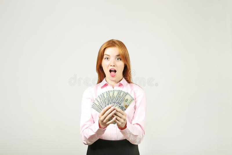 Atrakcyjny młody bizneswoman pozuje z wiązką USD spienięża wewnątrz ręki pokazuje pozytywne emocje i szczęśliwego wyraz twarzy zdjęcia stock