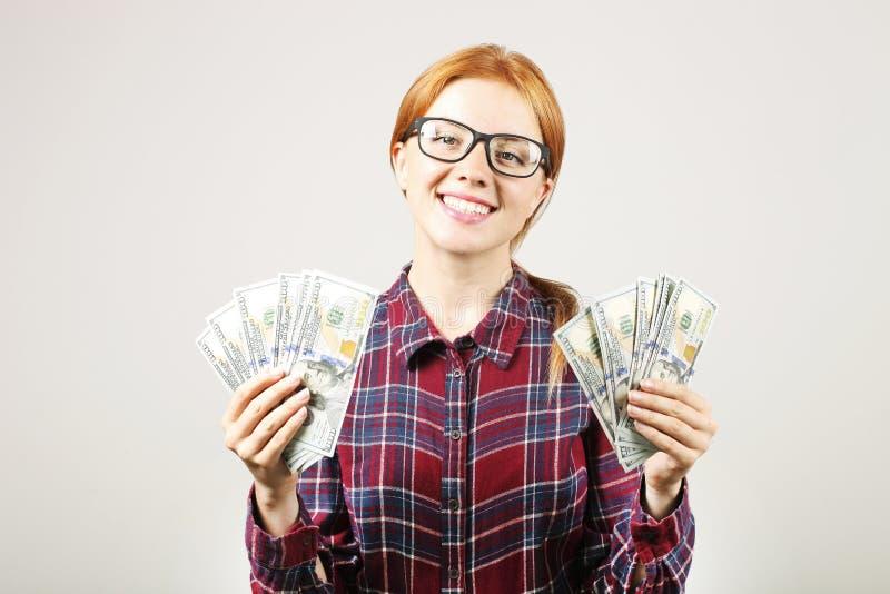 Atrakcyjny młody bizneswoman pozuje z wiązką USD spienięża wewnątrz ręki pokazuje pozytywne emocje i szczęśliwego wyraz twarzy zdjęcie stock