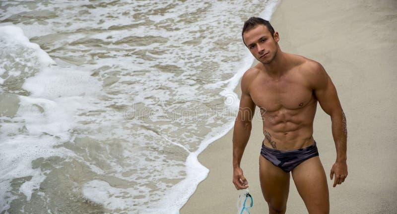 Atrakcyjny młody bodybuilder w kostiumu kąpielowym na plaży zdjęcie stock