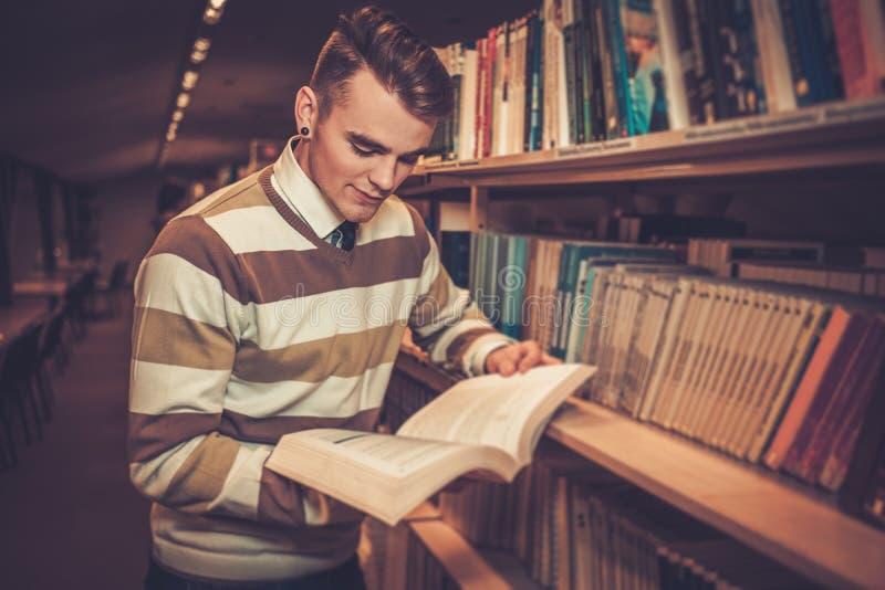 Atrakcyjny młody człowiek czyta książkę w bibliotece uniwersyteckiej fotografia royalty free