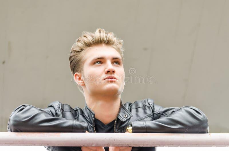 Atrakcyjny młody człowiek jest ubranym czarną skórzaną kurtkę obraz stock
