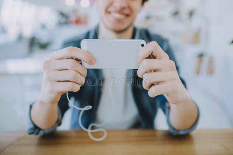 Atrakcyjny młody człowiek lub freelance siedzi w kawiarni i używa jego wiszącą ozdobę zdjęcia royalty free
