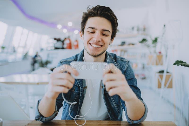Atrakcyjny młody człowiek lub freelance siedzi w kawiarni i używa jego wiszącą ozdobę zdjęcie royalty free