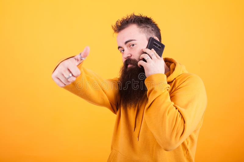 Atrakcyjny młody człowiek opowiada na telefonie i pokazuje aprobaty z długą brodą podpisuje żółtego tło obraz royalty free