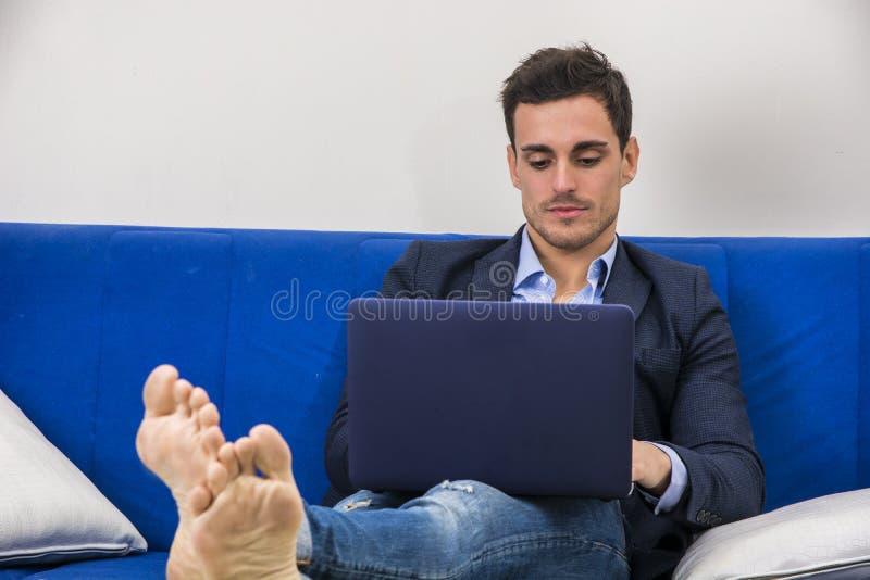 Atrakcyjny młody człowiek używa laptopu peceta na leżance obrazy royalty free