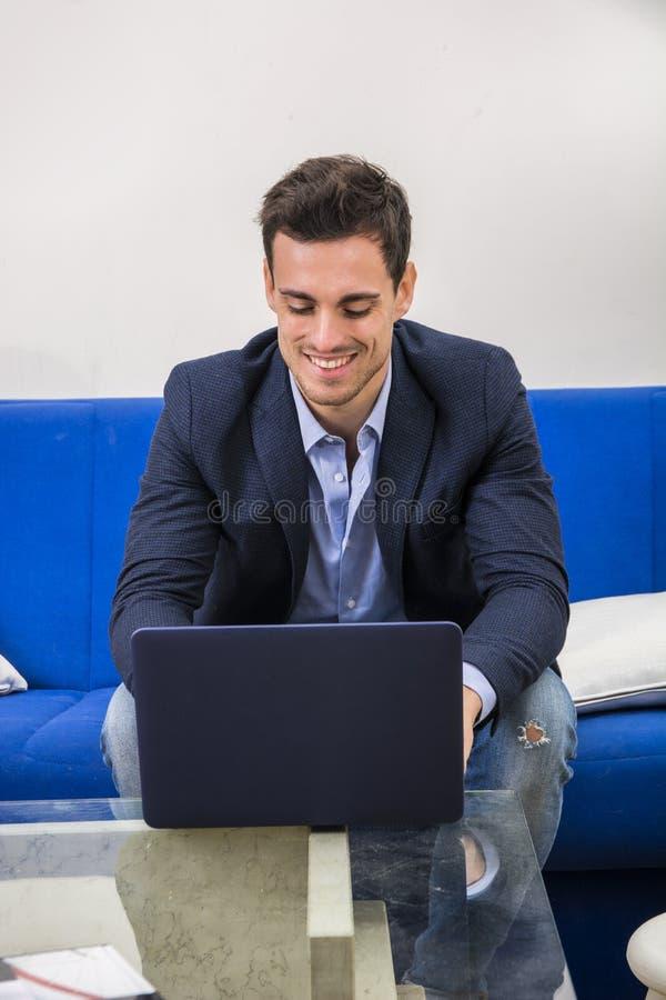 Atrakcyjny młody człowiek używa laptopu peceta na leżance obraz stock